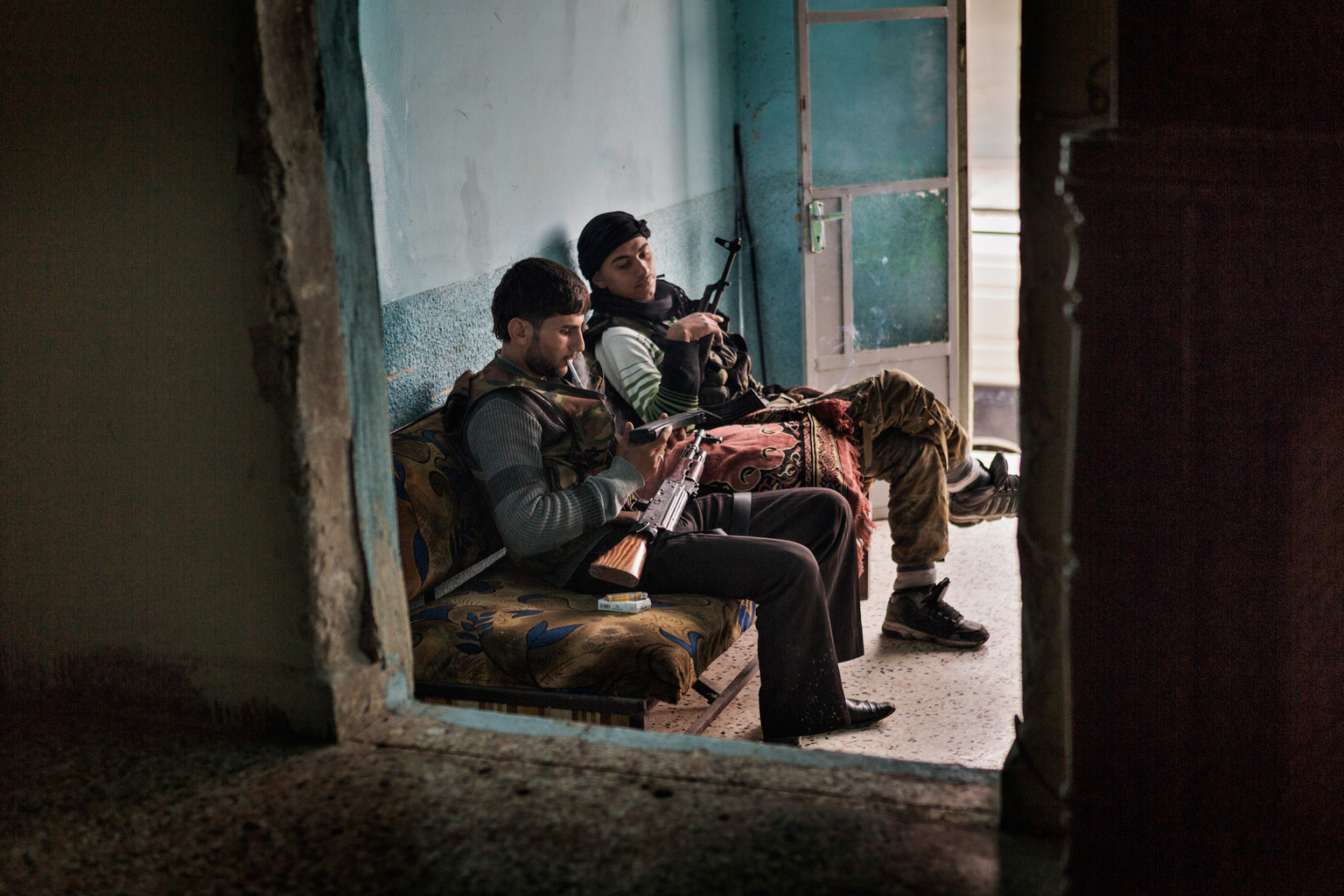 April 18, 2013, Sakhour, Aleppo. Members of a local FSA Khatiba [Free Syrian Army battalion] clean their weapons at their unit headquarters.