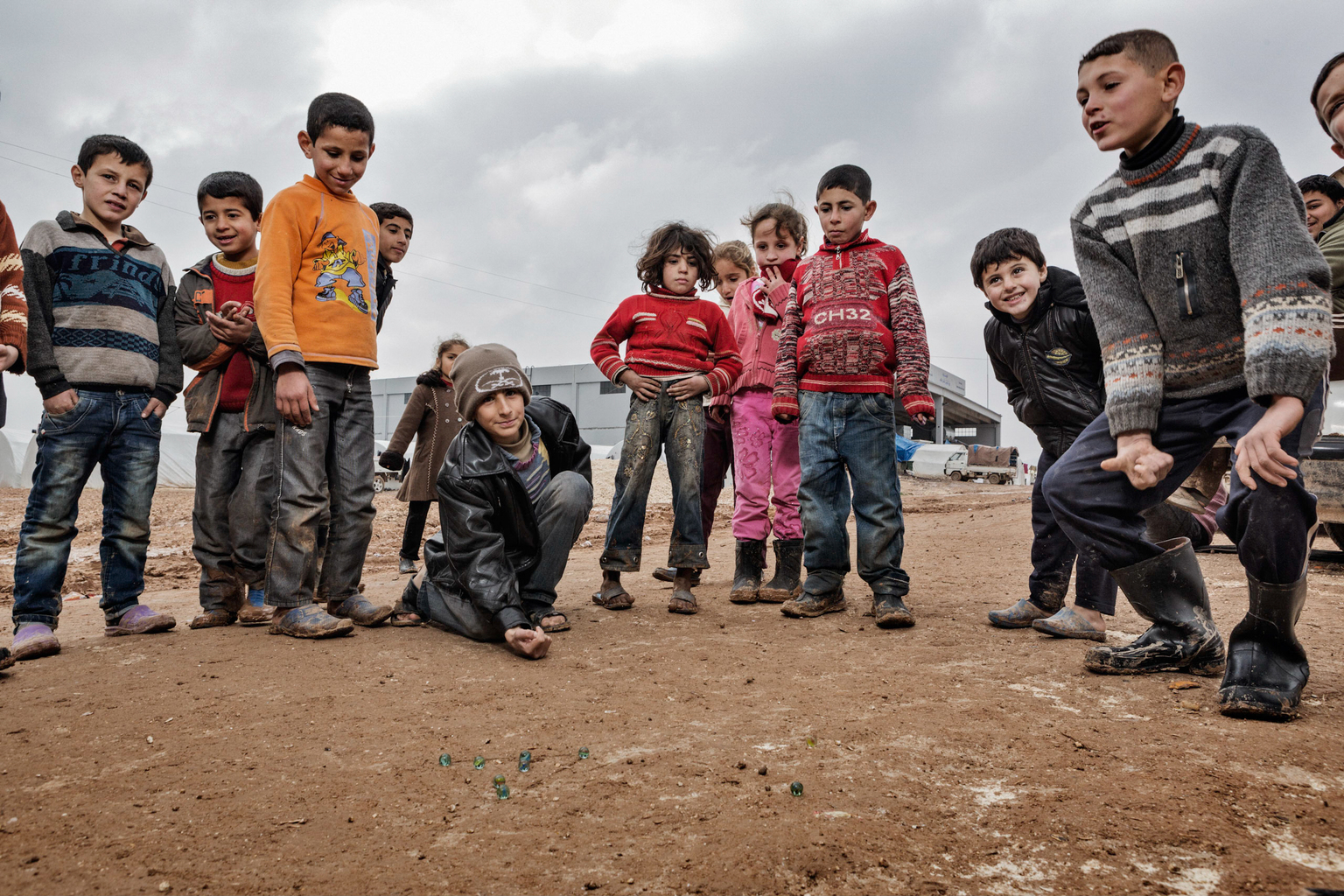 February 8, 2013, Bab al Salameh, Aleppo Province. Kids play marbles in the Bab al Salemeh refugee camp next to the Turkish border.