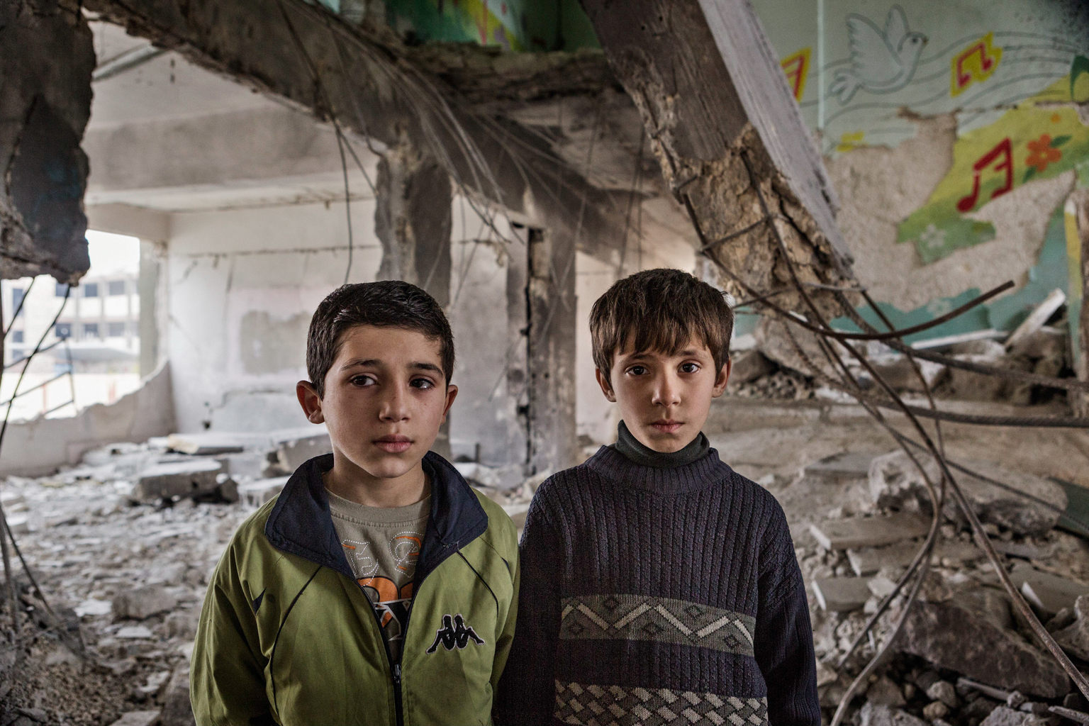 Febru ary 7, 2013, Tarik al Bab, Aleppo. Two boys stand for a portrait in a damaged school building.
