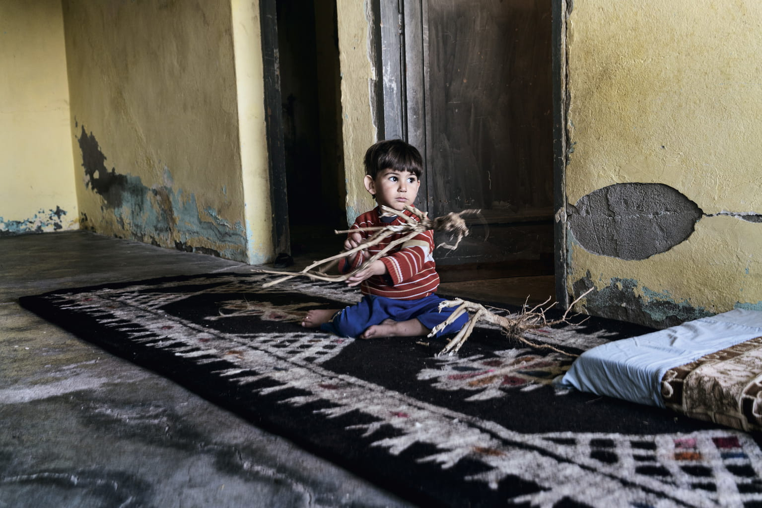 December 8, 2015, Reyhanli, Turkey. One of the boys plays with roots, the only toys the children have.