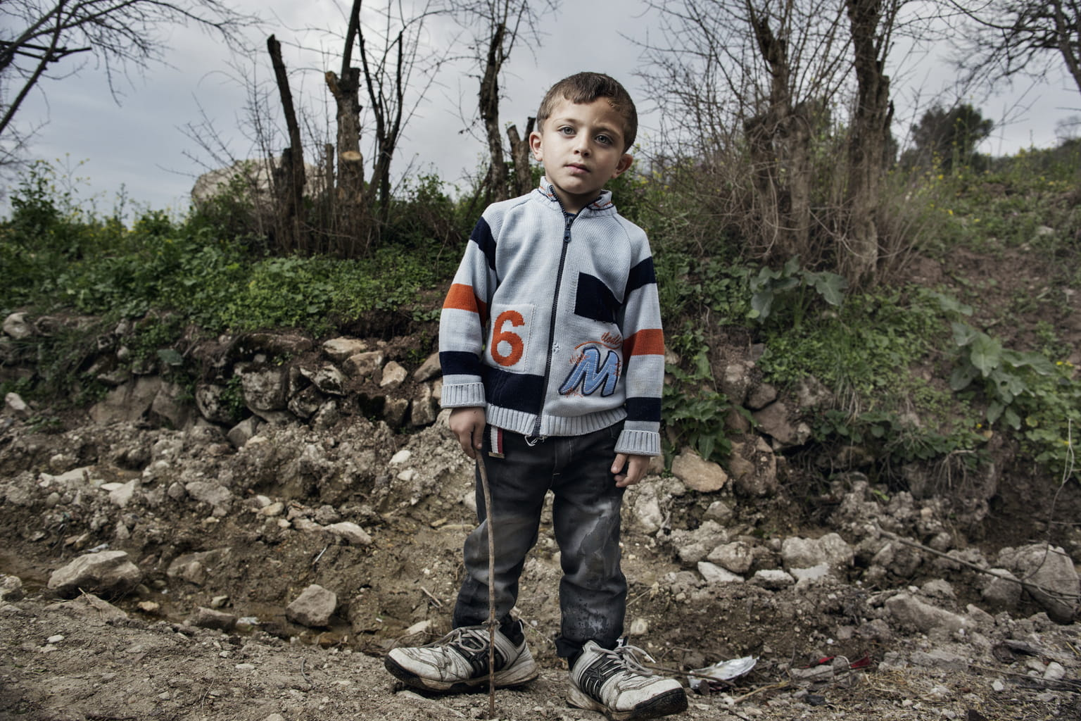 March 9, 2014, Gorentas, Turkey. A Syrian refugee boy plays with a stick. He is wearing his father's shoes because he has none that  t him. More than 200 Syrian refugee families live among this cluster of seven villages next to the Syrian/Turkish border.