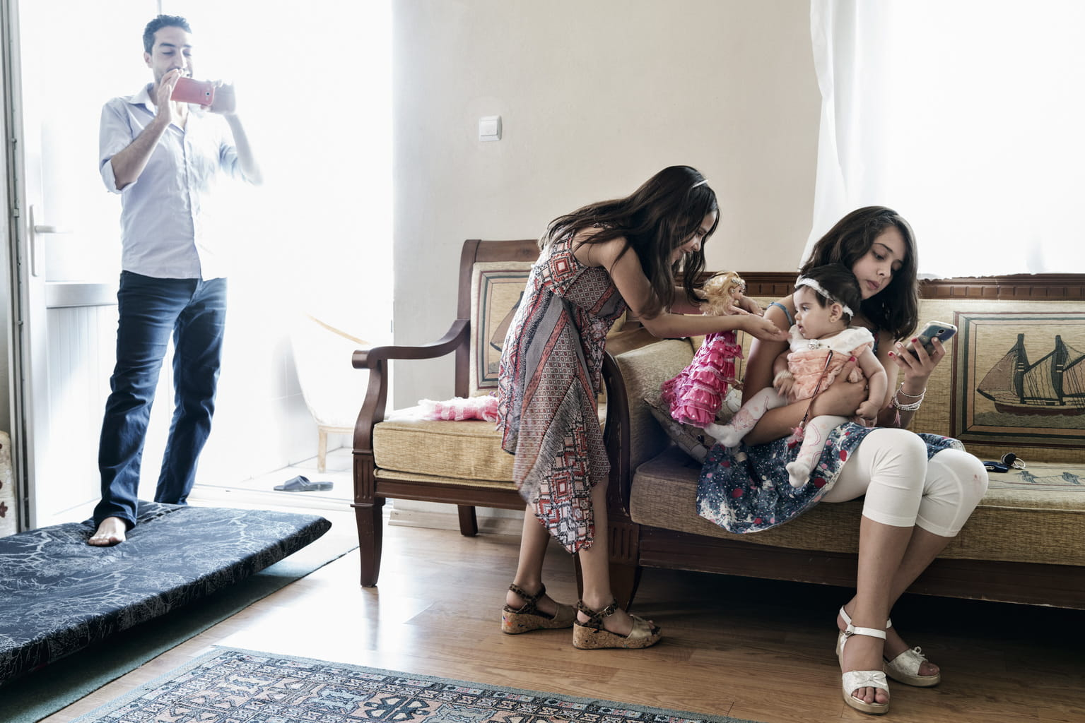 July 30, 2016, Gaziantep, Turkey. Syrian refugee Taher Hamada takes photos as his nieces, who live in the U.S., care for his four-month-old daughter, Tamara, at his apartment in southern Turkey.