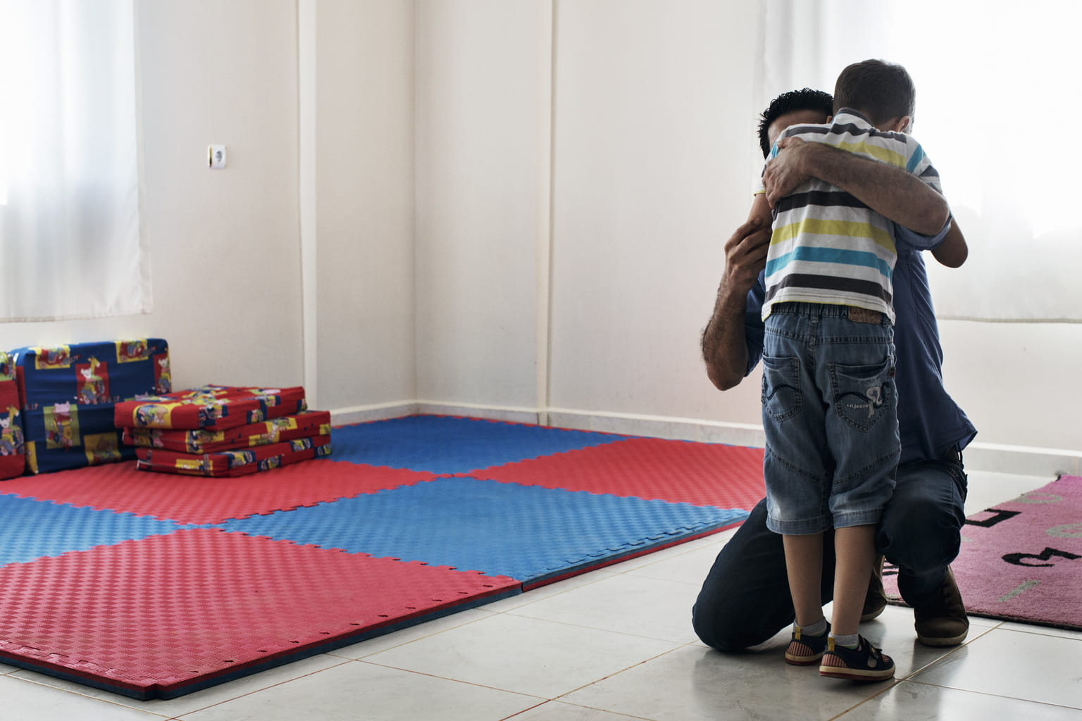 September 17, 2015, Reyhanli, Turkey. A therapist hugs an autistic boy during a therapy session.