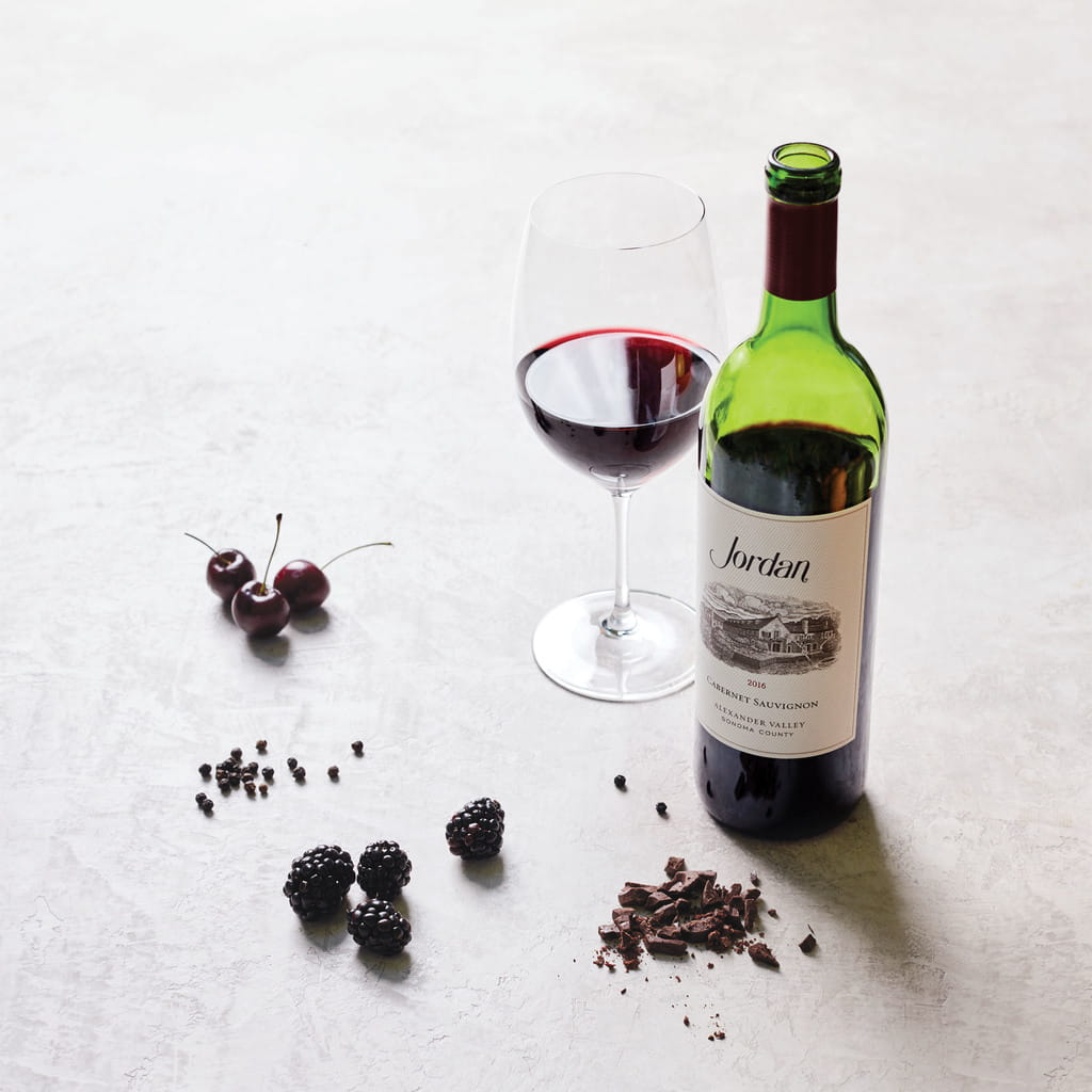 Bottle of 2016 Jordan Cabernet Sauvignon on a table with typical aromatics: cherries, blackberries, peppercorns and chocolate