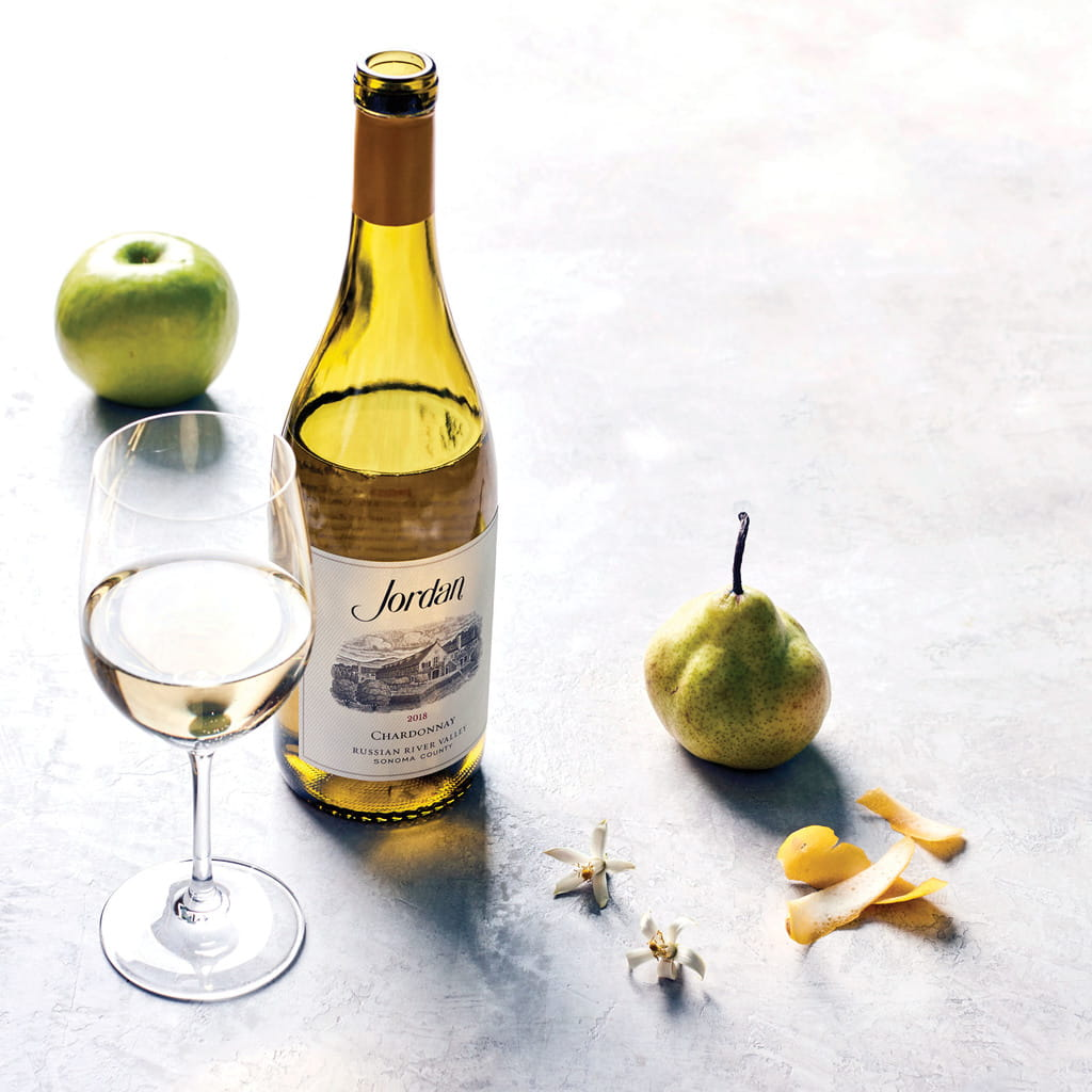 Bottle of 2018 Jordan Chardonnay on a table with typical aromatics: green apple, pear, lemon peel and citrus blossom