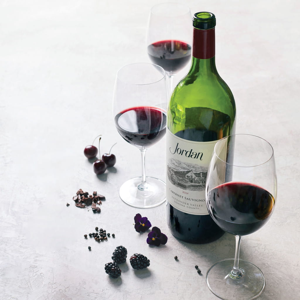 Magnum bottle of 2014 Jordan Cabernet Sauvignon on a table with typical aromatics: black cherries, chocolate, peppercorns, blackberries and violets