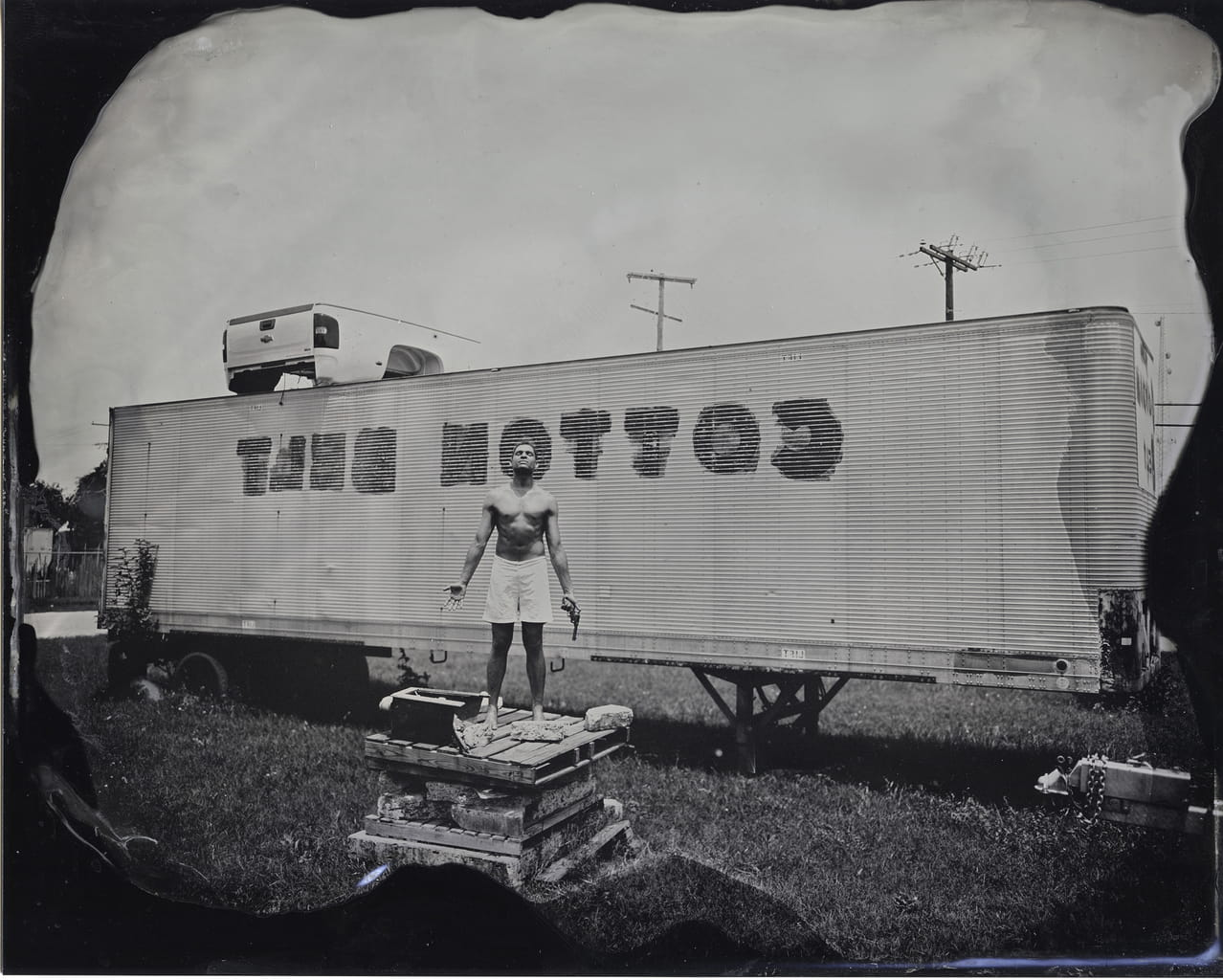 Adam W. McKinney, as Mr. Fred Rouse, standing in the site in which Mr. Rouse was lynched (Fort Worth, TX, 1921). From the series SCAB.