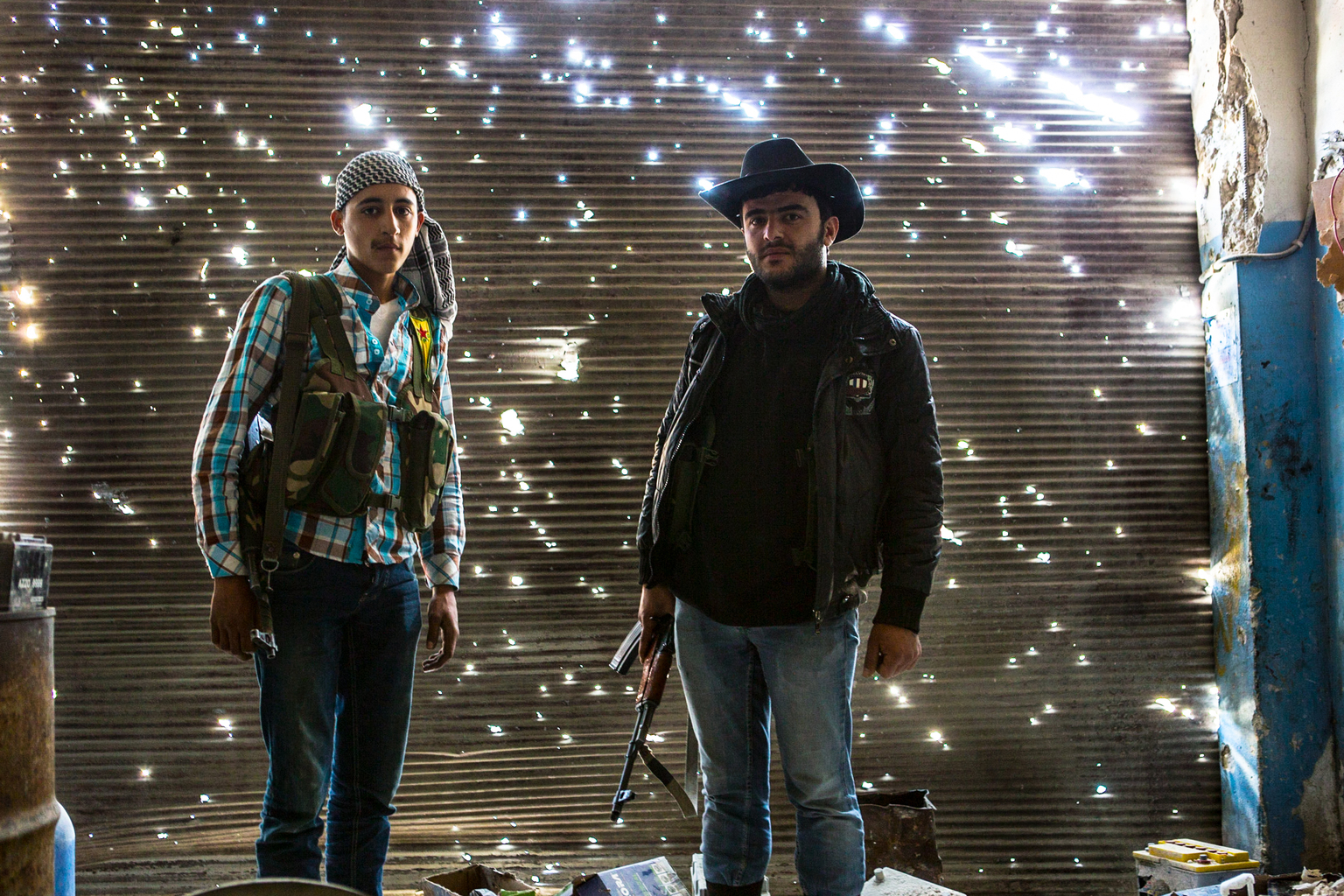 April 20, 2013, Sheikh Maqsood, Aleppo. Two Kurdish fighters stand in a damaged garage on the front line with Syrian Government forces.