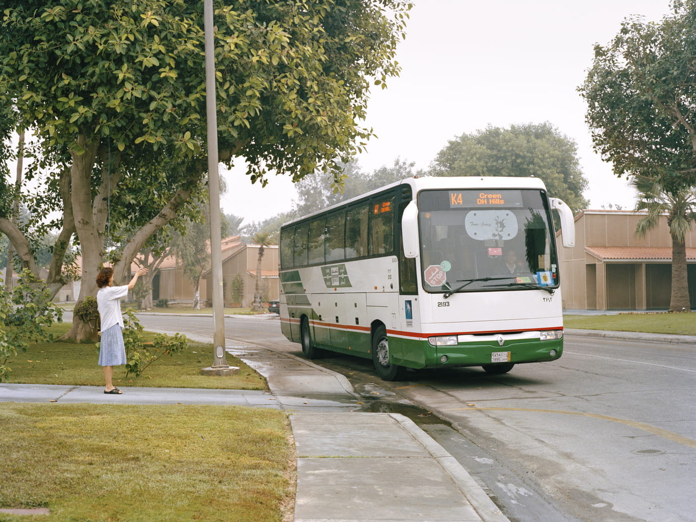 A mother waves goodbye to her daughter as she leaves for Dhahran Elementary School.